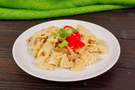 Wholemeal pasta baked with cabbage on a wooden table