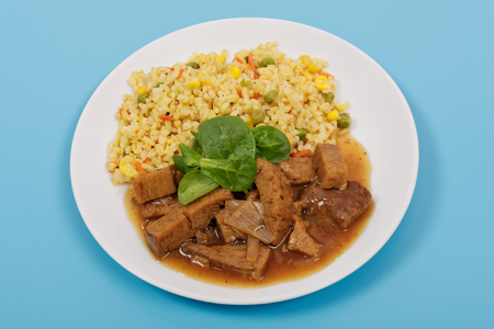 Tempeh with tomato sauce and millets on a blue background Standard-Bild