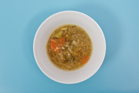 Miso vegetable soup with vegetables on a blue background