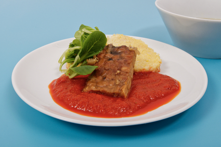Tempeh with tomato sauce and dumplings on a blue background Stock Photo