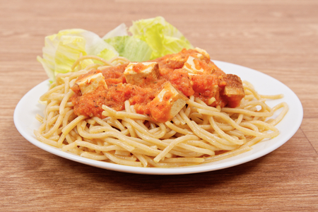 Bolognese spaghetti with tofu on a wooden table Reklamní fotografie