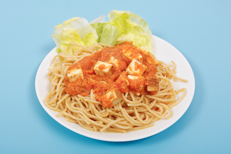 Bolognese spaghetti with tofu on a blue background