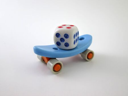 Little Skateboard Toy With White Little Cube Dice On Yourself 免版税图像