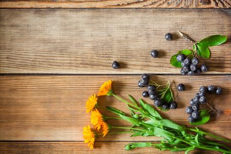 Calendulablumen und Aroniumbeeren (schwarze Chokeberry) auf hölzernem Hintergrund in der rustikalen Art. Draufsicht. Standard-Bild - 61472597