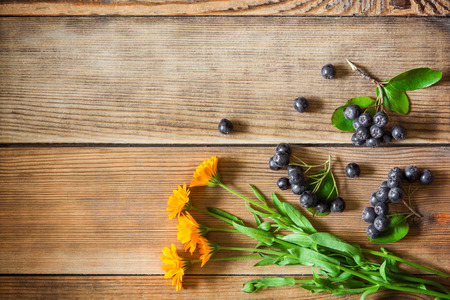 Calendula flowers and aronia berries (black chokeberry) on wooden background in rustic style. Top view.