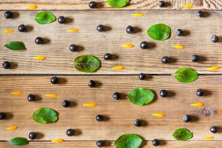 Aronia jagody (czarny arachidowy), nagietka płatki i liście na drewnianym tle w wieśniaku projektują. Widok z góry. Zdjęcie Seryjne