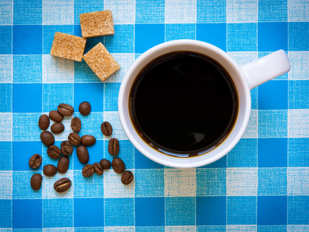checkered tablecloth: A cup of black coffee, brown sugar cubes and coffee beans on a checkered tablecloth. Top view. Stock Photo