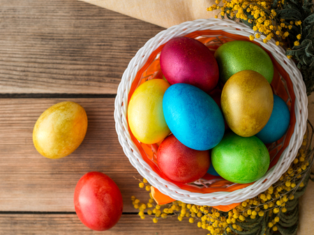 Colorful painted easter eggs in basket and mimosa flowers on rustic wooden table. Vintage holiday still life. Selective focus.