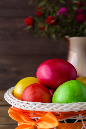Colorful painted easter eggs in basket and vase with flowers on rustic wooden table. Vintage holiday still life. Selective focus.