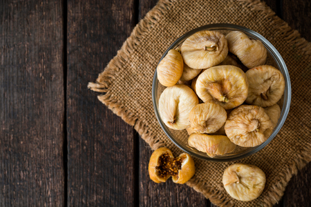 Dried figs in glass bowl on wooden background. Selective focus. Rustic style.