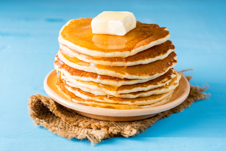 Pancakes with butter and honey on blue wooden table. Selective focus. Stock Photo