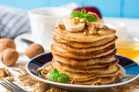 Pancakes with banana, honey, walnuts and mint on plate. Selective focus.