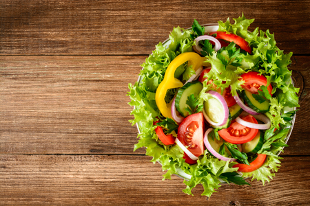 Fresh vegetable salad with greens on wooden table. Healthy vegetarian food. Top view. Stock Photo