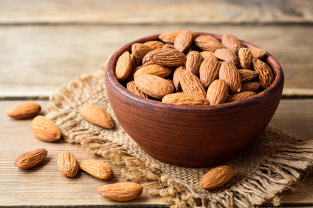 Almonds in ceramic bowl on wooden background. Selective focus. Imagens
