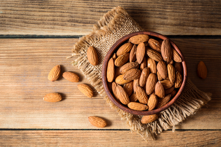 Almonds in ceramic bowl on wooden background. Top view.