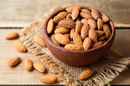 Almonds in ceramic bowl on wooden background. Selective focus. Stock Photo