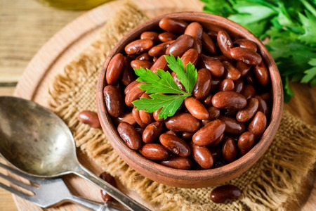 Boiled red beans in ceramic bowl. Selective focus. Stock Photo