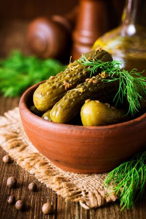 Pickled cucumbers with dill in ceramic bowl on dark rustic wooden table. Selective focus.