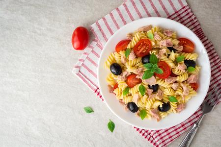 De pastasalade van Fusilli met tonijn, tomaten, zwarte olijven en basilicum op grijze steenachtergrond. Bovenaanzicht.