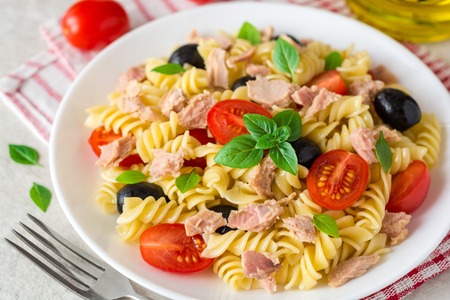 Fusilli pasta salad with tuna, tomatoes, black olives and basil on gray stone background. Selective focus.