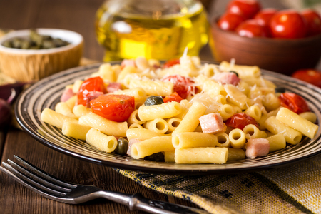 Pasta with bacon, garlic, tomatoes, capers and parmesan cheese in plate on dark wooden background. Selective focus.