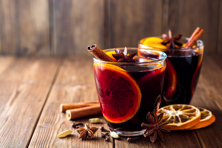 Two glasses of christmas mulled wine with oranges and spices on wooden background. Selective focus.