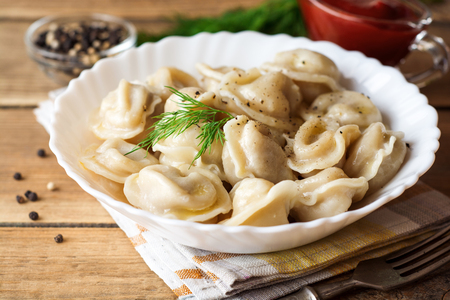 Russian meat dumplings pelmeni with dill on wooden rustic background. Selective focus.