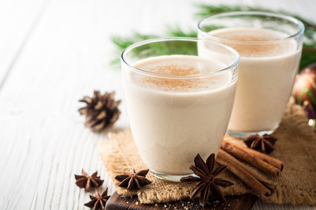 Homemade eggnog with grated nutmeg and cinnamon on white wooden table. Traditional Christmas drink. Selective focus. Stock Photo