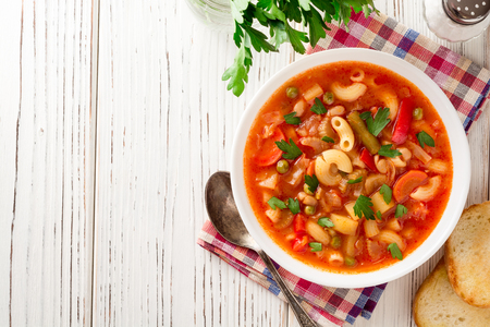 Italian minestrone soup on white wooden background. Top view.