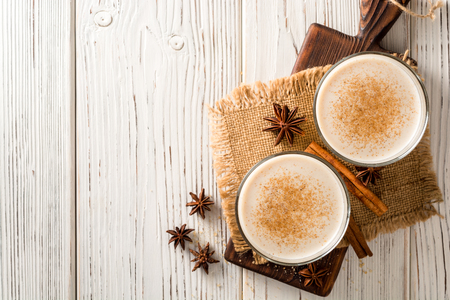 Homemade eggnog with grated nutmeg and cinnamon on white wooden table. Traditional Christmas drink. Top view. Stock Photo