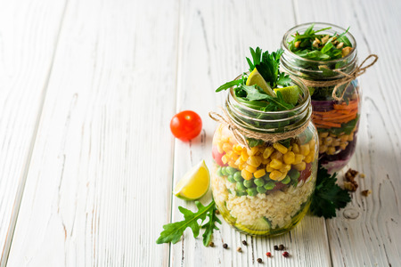 Healthy homemade salads with chickpeas, bulgur and vegetables in mason jars on white wooden background. Selective focus. Copy space.