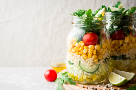 Healthy homemade salads with bulgur, vegetables and lime in mason jars on grey stone background. Selective focus.