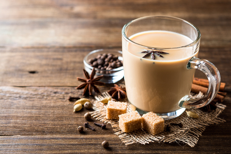 Indian masala chai on rustic wooden table. Selective focus. Copy space. Stock Photo