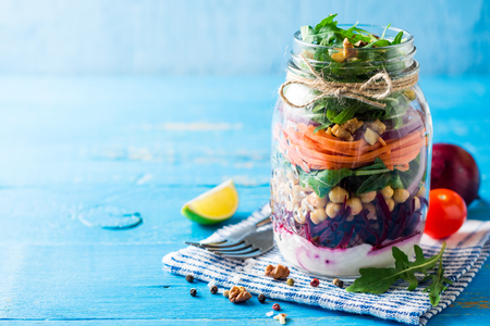 Healthy homemade salad with chickpeas, vegetables and walnuts in glass jar on blue background. Selective focus. Copy space.