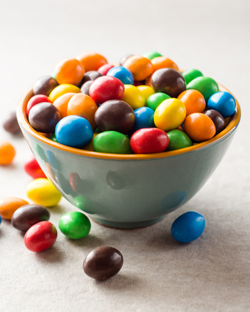 Colorful chocolate buttons in bowl on gray stone background. Selective focus. Stock Photo