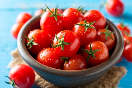 Cherry tomatoes in ceramic bowl on blue rustic wooden background. Selective focus.