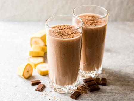 Chocolate banana smoothie in glass on gray stone background. Selective focus.