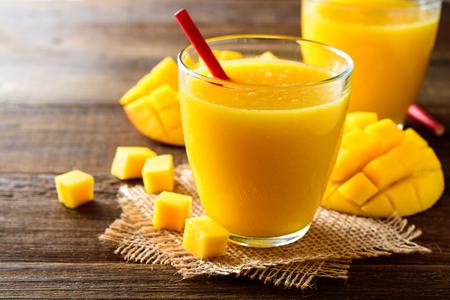 Mango smoothie in glass on dark wooden background. Selective focus.