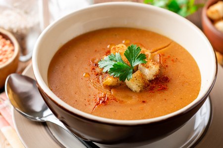 Red lentil cream soup with croutons in bowl on wooden table. Selective focus. Zdjęcie Seryjne