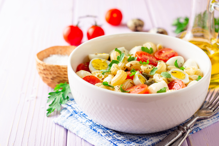 Pasta salad with quail eggs, mozzarella, cherry tomatoes and capers in bowl on purple wooden background. Selective focus.