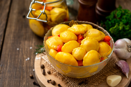 Marinated patty pan squash in glass bowl on dark rustic wooden