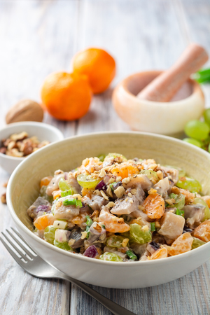 Salad with herring, tangerines, grapes, onions and walnuts in bowl on wooden table. Selective focus. Foto de archivo