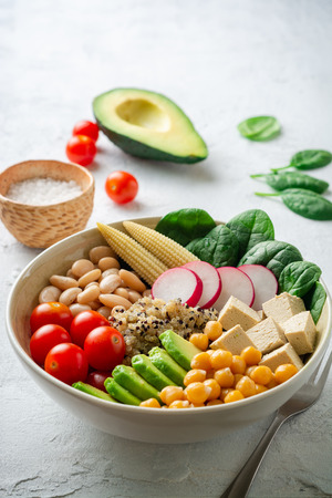 Healthy vegan buddha bowl with spinach, tomato, chickpea, quinoa, radish, beans, avocado, mini corn and tofu cheese on concrete