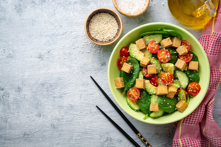 Vegan salad with spinach, cucumber, tomatoes, avocado, fried tofu and sesame. Top view. Copy space.