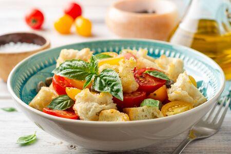 Ensalada italiana tradicional Panzanella con tomates cherry, pan, alcaparras y albahaca en un recipiente sobre la mesa de madera. Enfoque selectivo.