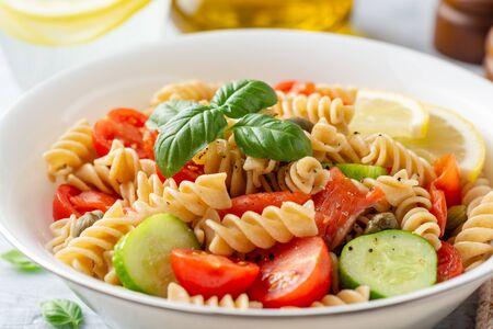 Ensalada de pasta integral con pepinos, tomates cherry, salmón salado y alcaparras sobre hormigón
