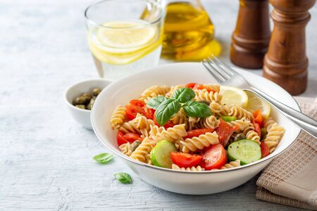 Whole wheat pasta salad with cucumbers, cherry tomatoes, salted salmon and capers on concrete