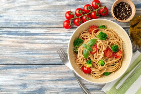 Whole wheat spaghetti pasta with broccoli, cherry tomatoes and basil in bowl on wooden 写真素材