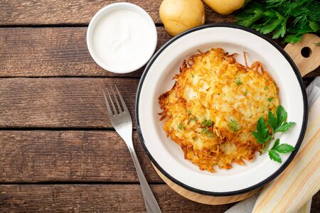 Potato pancakes or latkes or draniki in plate on dark wooden table. Фото со стока