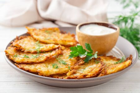 Potato pancakes or latkes or draniki with sour cream in plate on white wooden table. Selective focus.